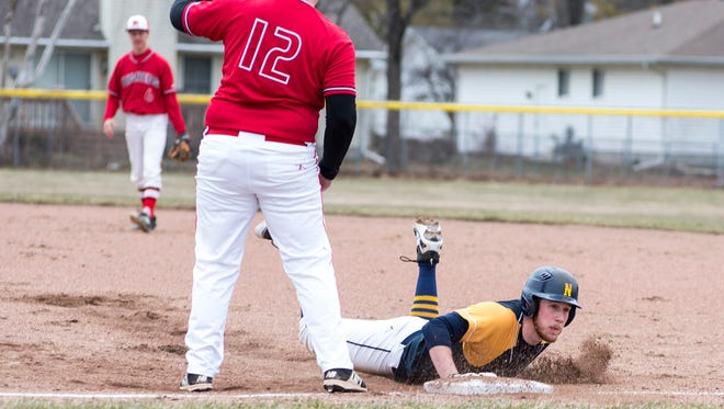 Port Huron Northern right fielder Bryce Reeves slides back to first base just in time to avoid being tagged out by Port Huron first baseman Shawn Schomburg (12) during their baseball game at Port Huron Northern High School Wednesday, April 18.
