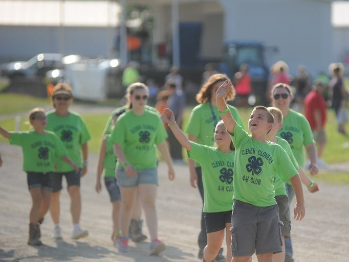 Ethan Wickham of Philo marches with Clever Clovers 4-H group during the opening ceremonies for the fair.