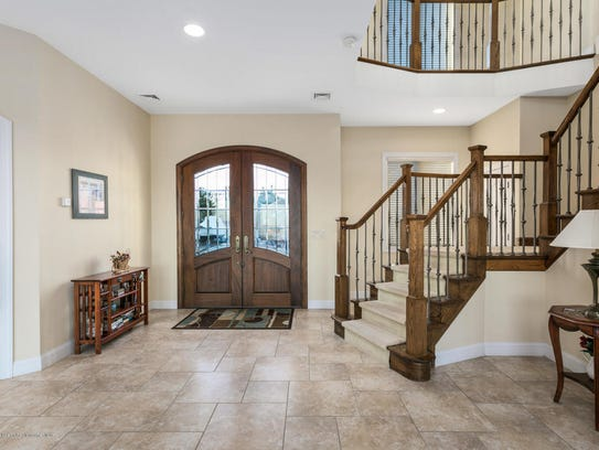 The grand foyer with tile flooring and double door