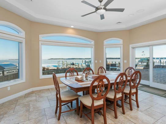 The dining room features oversized sliders and customized bay windows and recessed lighting.