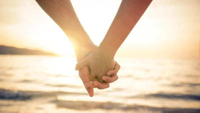 Getty Images/iStockphoto Holding hands at sunset.