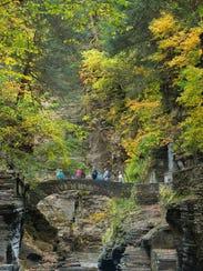 Walkers cross the bridge above Lucifer Falls in Robert