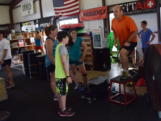 """Katherine Goins (second from left) brought her family, son Otis Goins (left), daughter Katie Goins (third from left) and husband Jeff Goins (far right) to the CrossFit Alexandria family workout. """"My daughter has never done CrossFit,"""" said Goins about Kati"""