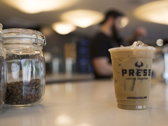 An iced latte sits on a counter at Press Coffee in