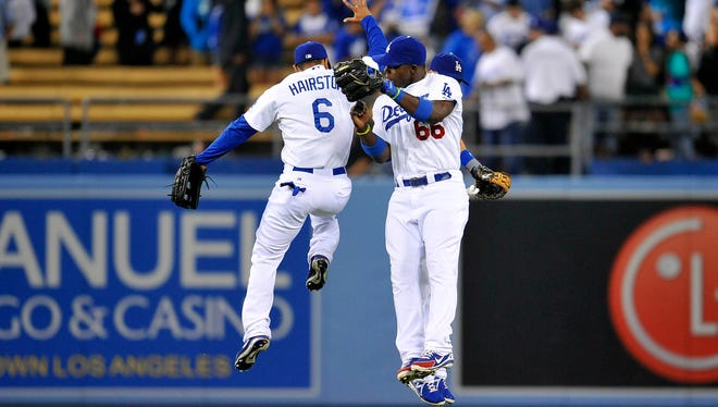 Los Angeles Dodgers outfielders Jerry Hairston Jr., Yasiel Puig and Skip Schumaker celebrate a 4-2 victory against the New York Mets at Dodger Stadium.
