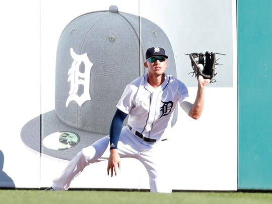 Detroit Tigers center fielder JaCoby Jones (21) shows that he caught the ball at the wall for an out during the sixth inning against Texas Rangers third baseman Adrian Beltre (not pictured) at Comerica Park on July 7, 2018.
