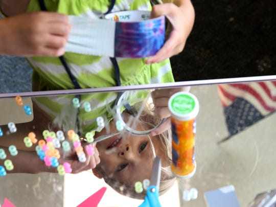 """Madelyn Kostraba decorates a medicine bottle with duct tape filled with what she called  """"alien food"""" at Soaring Stars held at Mount Morris Elementary School.The summer school program has helped children in rural areas keep on track academically."""