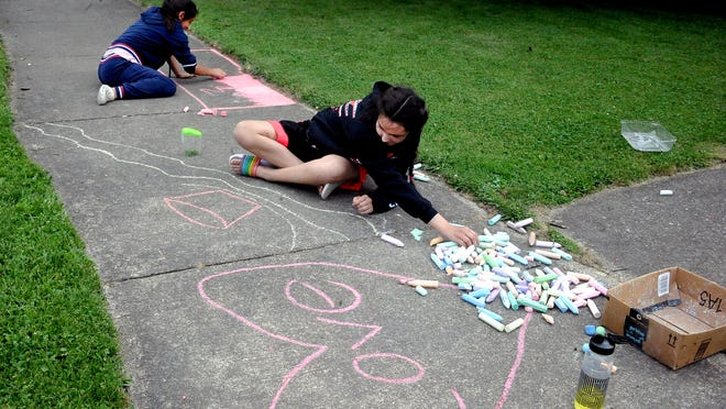 MacKenzie Martinez and Lilianna Roush spend some time creating artwork on the sidewalk in Orrville this week.