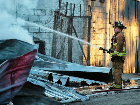 Memphis fire fighters keep an eye on the smoking remains after a massive fire destroyed a lumber manufacturing company in North Memphis Thursday morning. The two-alarm blaze was reported shortly before 3 a.m.  at the Charles O. Cox Corporation at 2392 Eldridge Avenue.