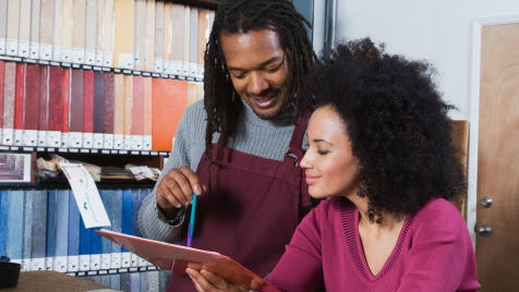 African woman and flooring sales clerk looking at clipboard