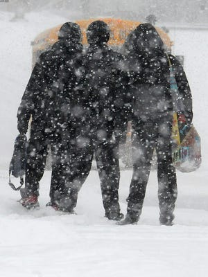 Three Crestline students wait for the bus last winter as the snow falls.