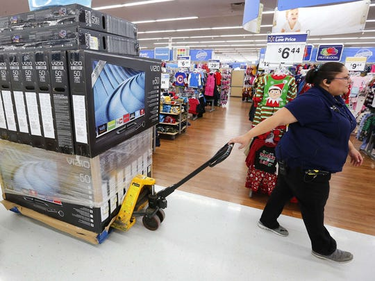 Walmart department manager Vanessa De La Cerda pulls a stack of television inventory on Tuesday at the Windsor Heights Walmart in advance of the Black Friday shopping rush.