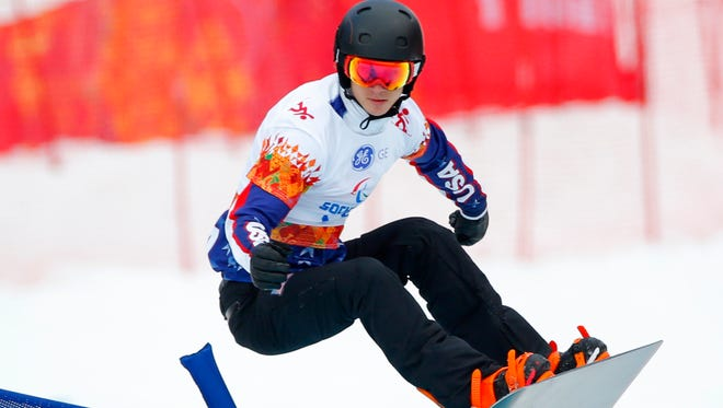 Evan Strong of the US competes during the men's para-snowboard cross, standing event at the 2014 Winter Paralympic, Friday.