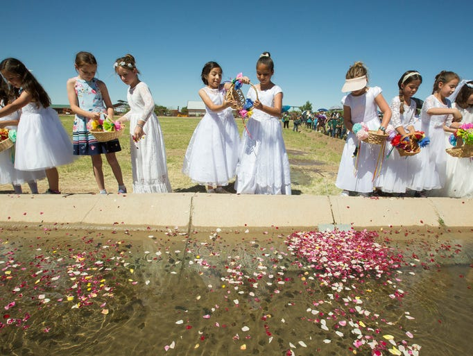 Students from Holy Cross Catholic School scatter flower