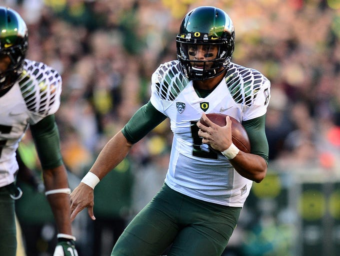 Mariota dodges defender on a run in Oregon's win over Colorado.