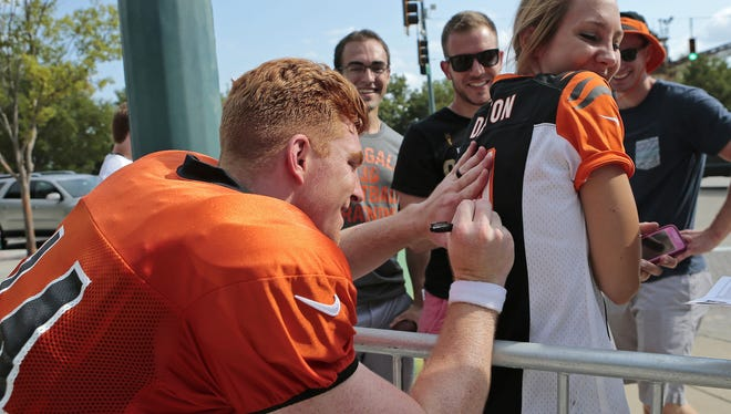 """Quarterback Andy Dalton (14) gives an autograph to a fan wearing his jersey after practice on day four of training camp at the Cincinnati Bengals training facility in downtown Cincinnati, on Monday, Aug. 3, 2015. The fan asked, """"Andy, can you sign my jersey?"""" to which he responded, """"You mean my jersey?"""""""
