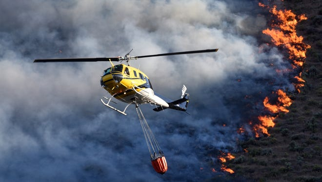 Adam Eschback/The Idaho Press-Tribune Emergency responders dump water onto a wildfire near Celebration Park south of Melba, Idaho on June 6. Authorities blamed the fire on a campfire set in an area where campfires were prohibited.