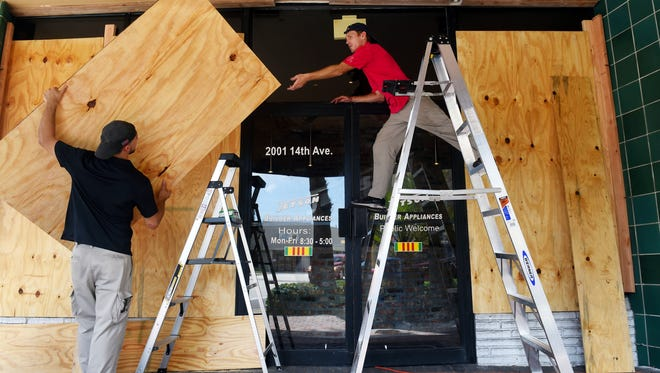 Jared Farias (left) and A.J. Flinchum place the last few plywood boards to the Jetson Builder Appliances storefront in downtown Vero Beach on Sept. 6, 2017, in preparation for Hurricane Irma. The storm is a Category 5 hurricane with maximum sustained winds near 185 mph.