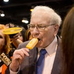 Berkshire Hathaway Chairman and CEO Warren Buffett is surrounded by shareholders and news media as he eats an ice cream bar before the annual shareholders meeting Saturday in Omaha.