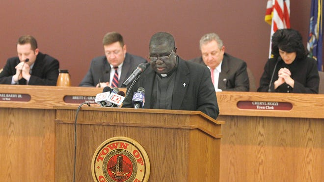 The Rev. Peter Enyan-Boadu, pastor from St. John the Evangelist Church, at podium, delivers a short prayer in front of the Greece Town Board at the start of a May meeting at Town Hall in Greece.