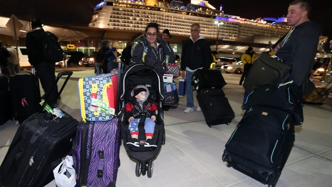Weary travelers aboard the Anthem of the Seas Royal Caribbean ship that was bound for Florida and the Bahamas and had to return home early after a powerful storm battered their liner with towering waves and high winds depart the ship at the Cape Liberty Cruise Port in Bayonne, New Jersey on Wednesday February 10, 2016.