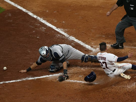 Houston Astros second baseman Jose Altuve (27) crosses home plate for the winning run as New York Yankees catcher Gary Sanchez (24) reaches for the ball during the ninth inning in game two of the 2017 ALCS playoff baseball series at Minute Maid Park on Saturday, Oct 14, 2017.