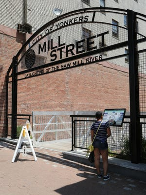 A visitor looks over an information display at the Warburton Avenue entrance to the new Mill Street courtyard and daylighting of the Saw Mill River.