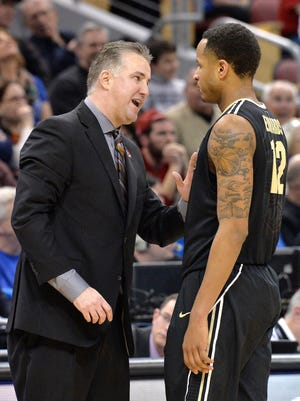 Purdue head coach Matt Painter, left, talks with Vince Edwards during the second half of an NCAA tournament second round college basketball game against Cincinnati in Louisville, Ky., Thursday, March 19, 2015. Cincinnati won in overtime 66-65.