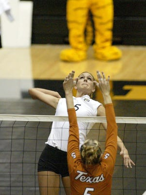 Christi Myers, a Raytown South graduate, leaps to spike the ball down in a volleyball game against Texas.