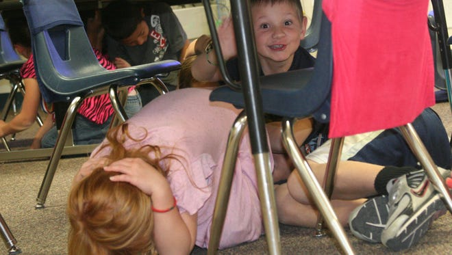 "Students in Jo Matheus' second-grade classroom get under their desks and show the ""drop, cover and hold on"" technique as they participate in the Great Nevada ShakeOut along with others throughout the state in 2012."