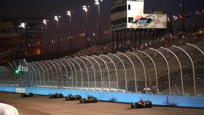 IndyCar drivers race down the front stretch in front of the main grandstands and timing tower during the Phoenix Grand Prix at ISM Raceway.