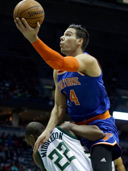 New York Knicks' Willy Hernangomez commits an offensive foul against Milwaukee Bucks' Khris Middleton (22) during the first half of an NBA basketball game, Wednesday, March 8, 2017, in Milwaukee. (AP Photo/Aaron Gash)