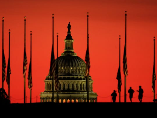The U.S. Capitol dome backdrops flags at half-staff