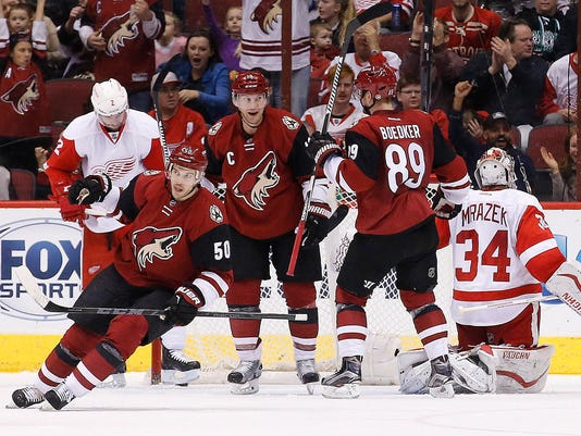 Arizona Coyotes' Mikkel Boedker (89), of Denmark, and Antoine Vermette (50) celebrate a goal by Shane Doan, middle, against Detroit Red Wings' Petr Mrazek (34), of the Czech Republic, as Red Wings' Brendan Smith (2) looks away from the celebration during the second period of an NHL hockey game Thursday, Jan. 14, 2016, in Glendale, Ariz. (AP Photo/Ross D. Franklin)