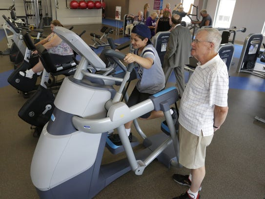 Lincoln Eichstadt, 9, tries out the new adaptive motion trainer as his grandfather Jim Eichstadt watches July 13 at the Oshkosh Community YMCA Downtown Center.