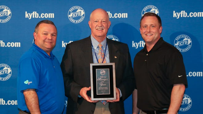 Chuck Osborne, KFB insurance vice president of agency support & marketing (left), and Adam Whiteside, KFB insurance agency support & marketing manager for District One (at right), present Chase Fulcher (center) with the 2016 District One Agency Manager of the Year Award.