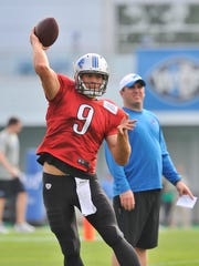 Matthew Stafford throws a pass with Jim Bob Cooter looking on.