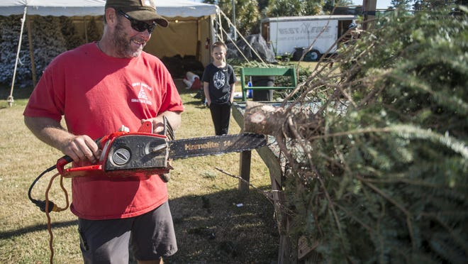 Luke Braxton, 9, watches as Chris McComas uses a chainsaw to trim branches from a fresh Christmas tree Monday morning at Snowy Mountain Christmas Trees at 2816 Washington Road. The business also has lots at 3818 Washington Road in Martinez and 850 Blanchard Road in Evans. Visit snowymountainchristmastrees.com for details.