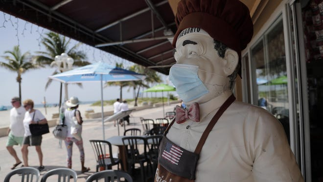 CORRECTS TO BROADWALK, INSTEAD OF BOARDWALK  A statue of a chef at Florio's of Little Italy restaurant wears a protective face mask on the Hollywood Beach Broadwalk during the new coronavirus pandemic, Thursday, July 2, 2020, in Hollywood, Fla. In hard-hit South Florida, beaches from Palm Beach to Key West will be shut down for the Fourth of July holiday weekend. Restaurants and businesses along the Boardwalk will remain open.