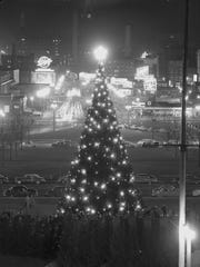 Milwaukee's municipal Christmas tree is lighted in a ceremony on Dec. 19, 1954, in MacArthur Square. This photo looks east from the tree down Kilbourn Ave.; the Milwaukee Auditorium (now Milwaukee Theatre), is at left.