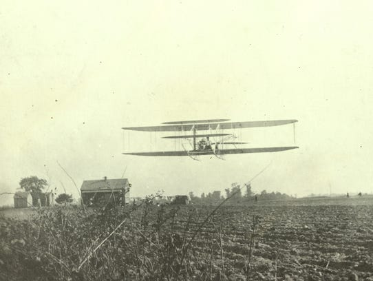 A Wright Flyer takes off over a cotton field at the