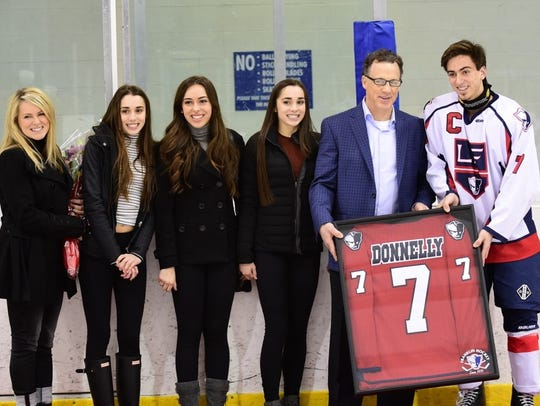 Mike Donnelly is presented a framed Franklin jersey