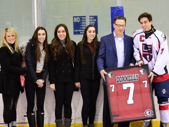 Mike Donnelly is presented a framed Franklin jersey by current Patriot captain Brendan Whitney as his wife, Debbie (far left) and daughters Paulina, Alexa and Micaela look on.