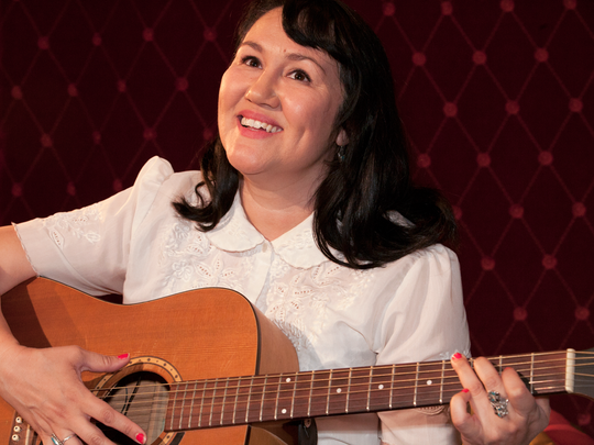 "Dilcia Yanez strums a guitar and sings in her role as Peggy in Space 55's musical ""Blue Galaxy."""