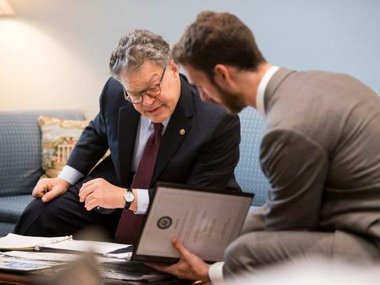 Sen. Al Franken speaks to energy policy adviser Blaise