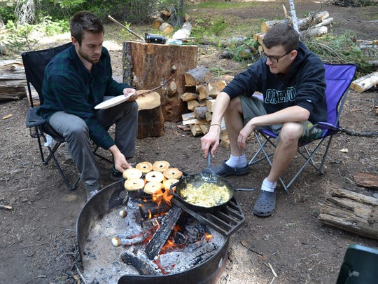 Tyler Dodds and Stefan O'Neill make breakfast over the fire at Mazama Campgrounds near Crater Lake National Park.