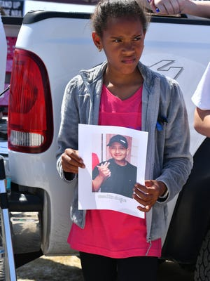 Aaliyah Devins holds a photo of a student killed at Marjory Stoneman Douglas High School on Feb. 14 during the March 24 March for Our Lives in Melbourne.