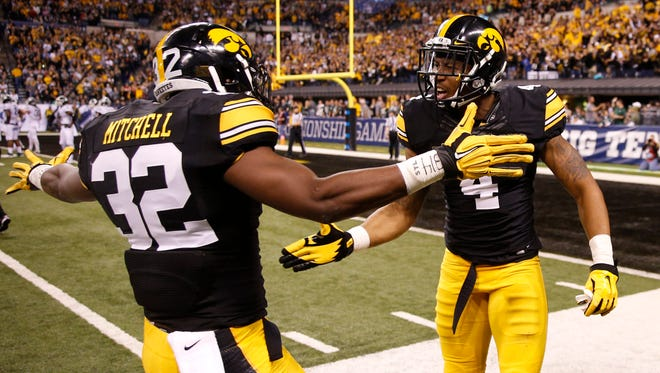 Iowa Hawkeyes wide receiver Tevaun Smith (4) and running back Derrick Mitchell Jr. (32) celebrate a touchdown during the third quarter against the Michigan State Spartans in the Big Ten Conference football championship game at Lucas Oil Stadium.