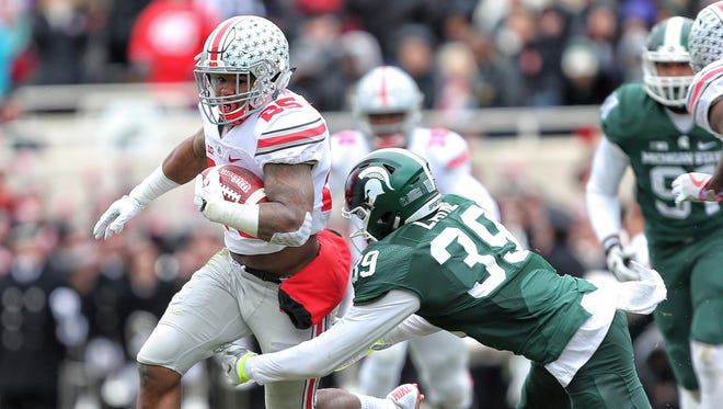 Ohio State running back Mike Weber carries the ball against Michigan State's Justin Layne in 2016 at Spartan Stadium, a 17-16 OSU win.