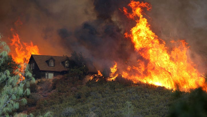 Flames from the Rocky Fire approach a house on July